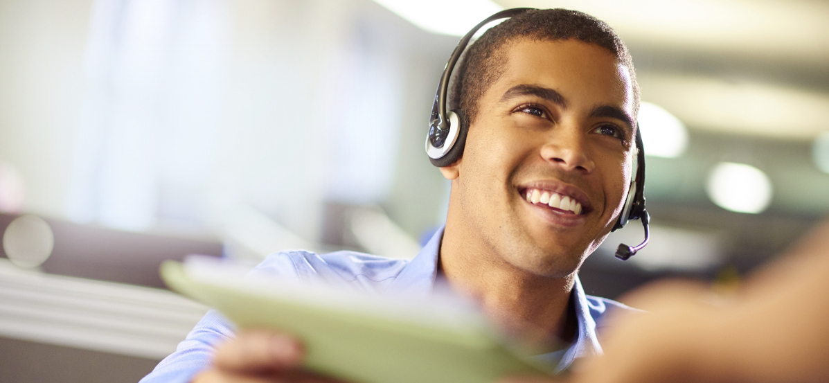 Moneytree customer service representative smiling in a call center. Moneytree offers a suite of services.