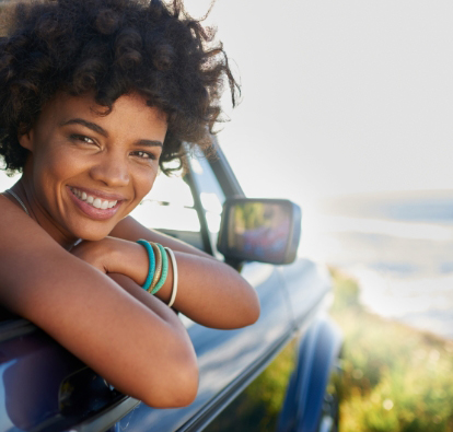 Smiling woman leaning out a car window at the beach
