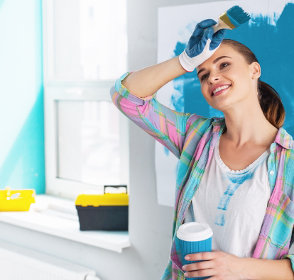 Smiling woman holding a paint brush in one hand and a coffee cup in the other