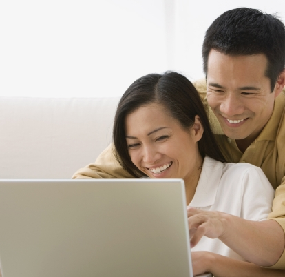 A smiling man hugging a woman from behind, while typing on a laptop.