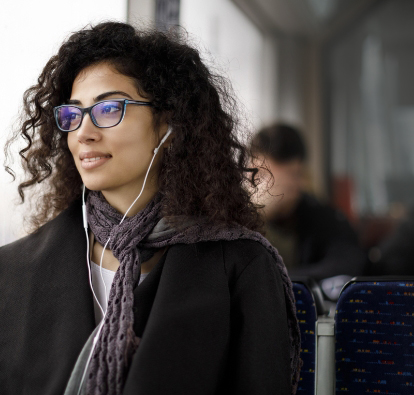Woman with glasses sitting in a bus, looking out of the window.