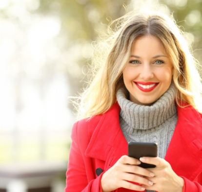 Smiling woman in red coat holding a cell phone