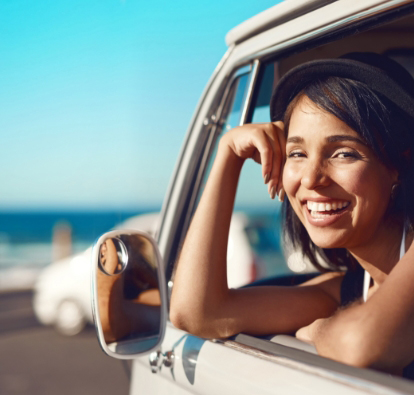 Smiling woman waring a hat leaning out a car window.