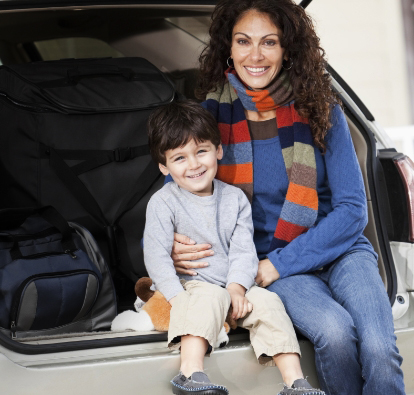 Image of a woman holding her little boy, both smiling, while sitting on the back bumper of their SUV. With luggage in the background.