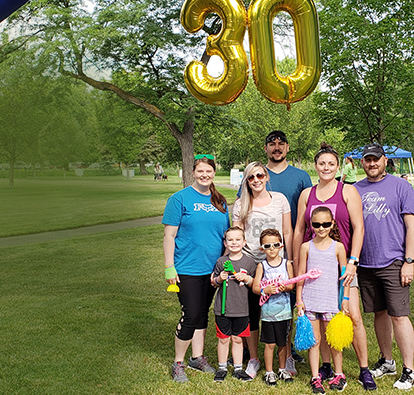 Picture of a family, posing for a group picture and smiling at a park.
