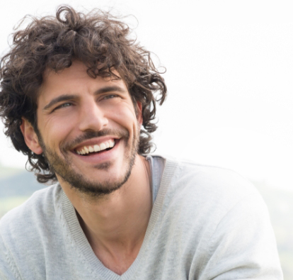Man smiling with a grey shirt.